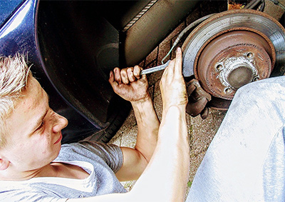 mechanic replacing brakes on vehicle